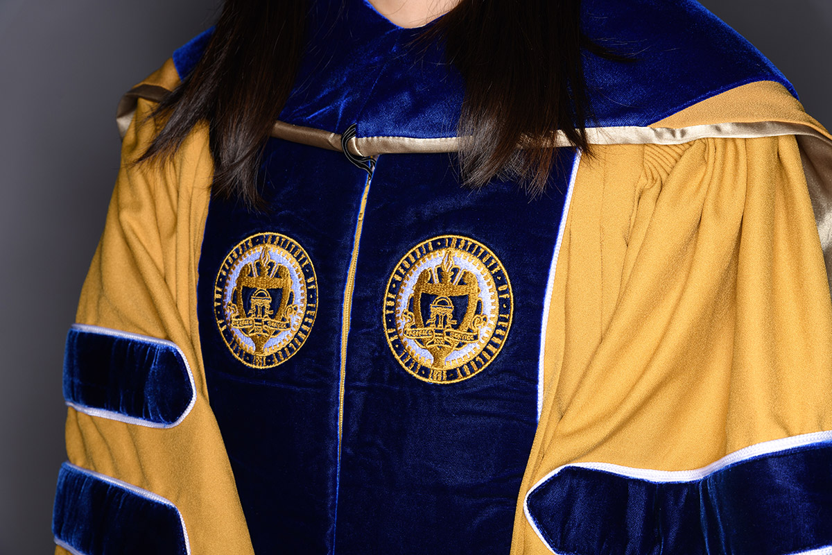 Closeup of Georgia Tech Ph.D. regalia in gold and navy blue with the seal of the Institute on the lapels.